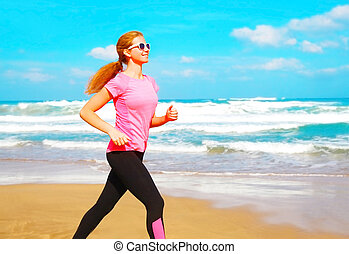Fitness woman is running along the beach near the sea on a summer day