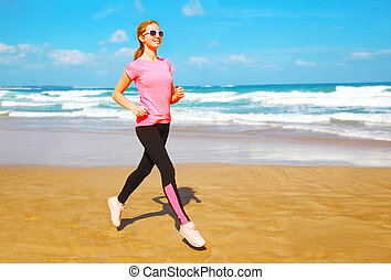 Fitness woman is running on the beach near the sea on a summer day