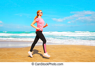 Fitness woman is running summer along the beach near the sea at summer day