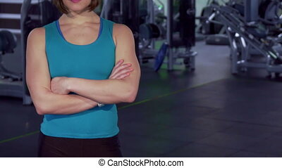 Fitness woman keeps arms crossed on her chest