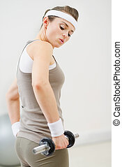 Fitness woman lifting dumb-bell in the gym