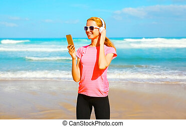 Fitness woman listens to music in a wireless headphones with smartphone on the beach