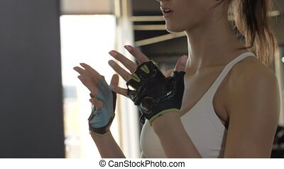 Fitness woman making warm up exercises hands for endurance training in gym club