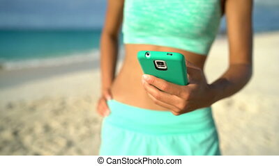 Fitness woman on beach using smartphone app on 4g or texting...