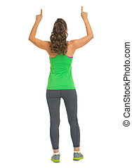 Fitness woman pointing up on copy space . rear view