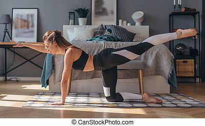 Fitness woman practising yoga doing bird dog exercise. - ...