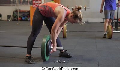 Fitness woman puts plate on barbell during weight lifting workout in gym