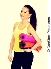 Fitness woman ready holding yoga mats.