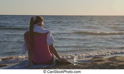 Fitness woman relaxing after workout routine listening music on beach