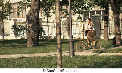 Fitness woman riding bicycle in city park on summer day. Woman bike park