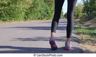 Fitness woman runner running away on the road