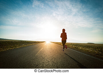 Fitness woman runner running on country road
