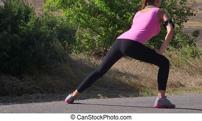 Fitness woman runner stretching before run on the road