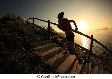 fitness woman runner trail running on seaside mountain...