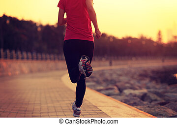 fitness woman running at seaside. woman fitness silhouette...