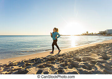 Fitness Woman Running by the Ocean at Sunset