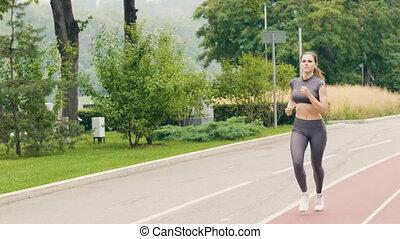 Fitness woman running on summer park at morning jog. Sport...