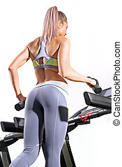 Fitness woman running on treadmill in gym