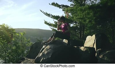 Fitness woman seats on the mountain rocks and drinks water