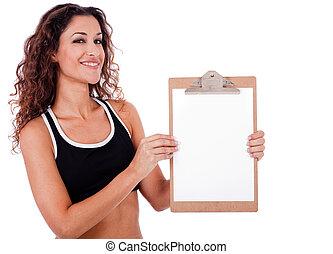 Fitness woman showing a blank clip board
