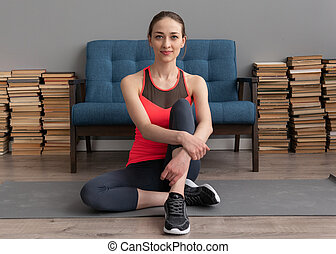 Fitness woman sitting on floor at home