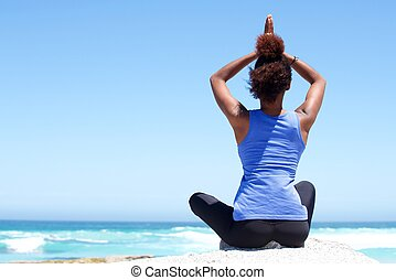 Fitness woman sitting outdoors in yoga pose