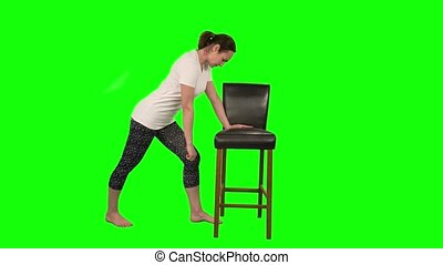 Fitness woman in white t-shirt standing in pose leaning on black chair and doing exercises for rehabilitation shoulder isolated at green screen in studio.