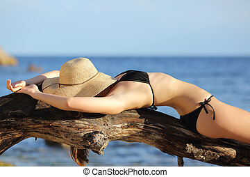 Fitness woman sunbathing on the beach sleeping