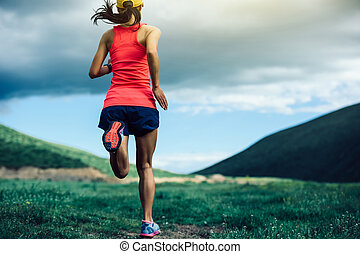 fitness woman trail runner running in mountains