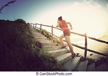 fitness woman trail runner running on seaside mountain ...