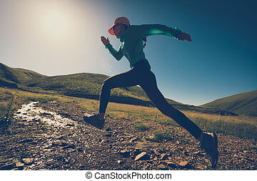 fitness woman trail runner running on grassland trail