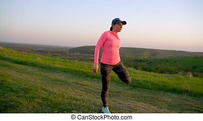 Fitness woman warms up and stretching outdoors before run
