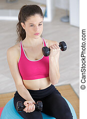 fitness woman with dumbbells in studio