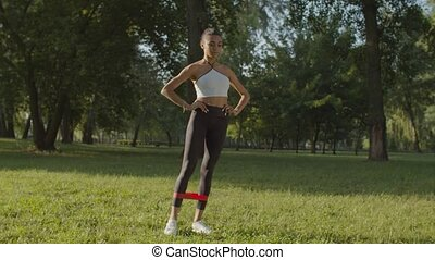 Concentrated motivated attractive sporty african american fitness woman working out, performing exercises for leg muscles with elastic resistance band in public park in rays of morning rising sun.