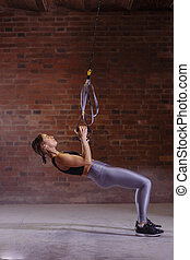 Fitness woman workout on TRX straps in gym. Crossfit style. Training TRX.