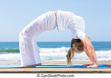 fitness woman yoga exercise on beach - fitness mature woman...