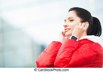 Fitness woman. Young lady in sportswear with earphones near a airport