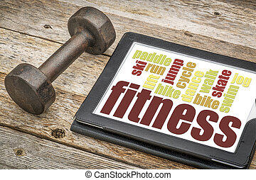 fitness word cloud on a digital tablet with a dumbbell