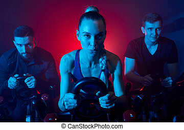 fitness workout people training on smart stationary bike indoors in gym