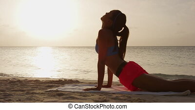 Fitness yoga woman stretching abdominals practicing morning sequence doing cobra pose or upward facing dog. Fit fitness girl stretching on beach at sunrise. Beautiful multiracial female model.