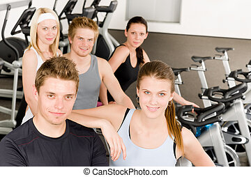 Fitness young group people at gym bicycle
