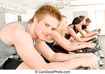 Fitness young man on gym bike spinning - Fitness group of...
