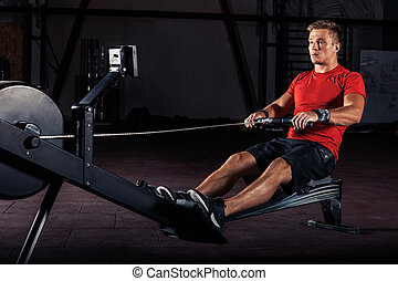 young man using rowing machine in the gym