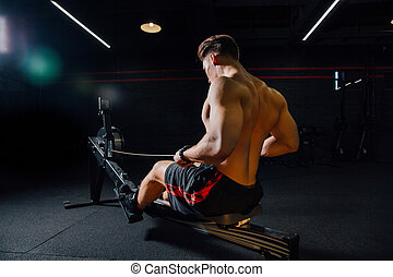 Fitness young man using rowing machine in the gym. Rower...