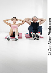 fitness - young woman and senior man doing abs in gym