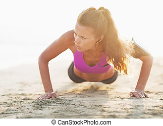 Fitness young woman doing push ups on beach