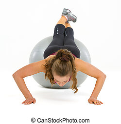 Fitness young woman doing push ups on fitness ball