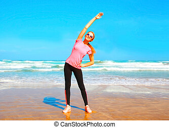 Fitness young woman doing stretching exercise on the beach near the sea at summer day