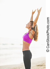 Fitness young woman in headphones rejoicing on beach