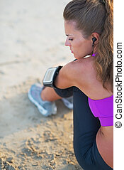 Fitness young woman in headphones sitting on beach